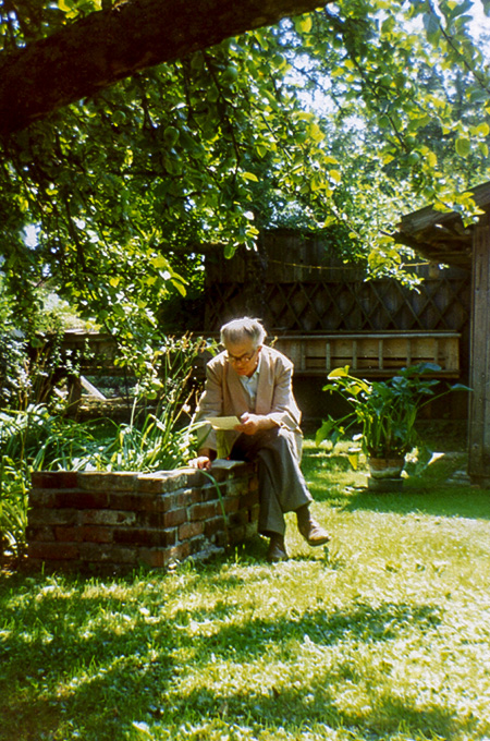 Joseph Mader liest ein Buch im Garten